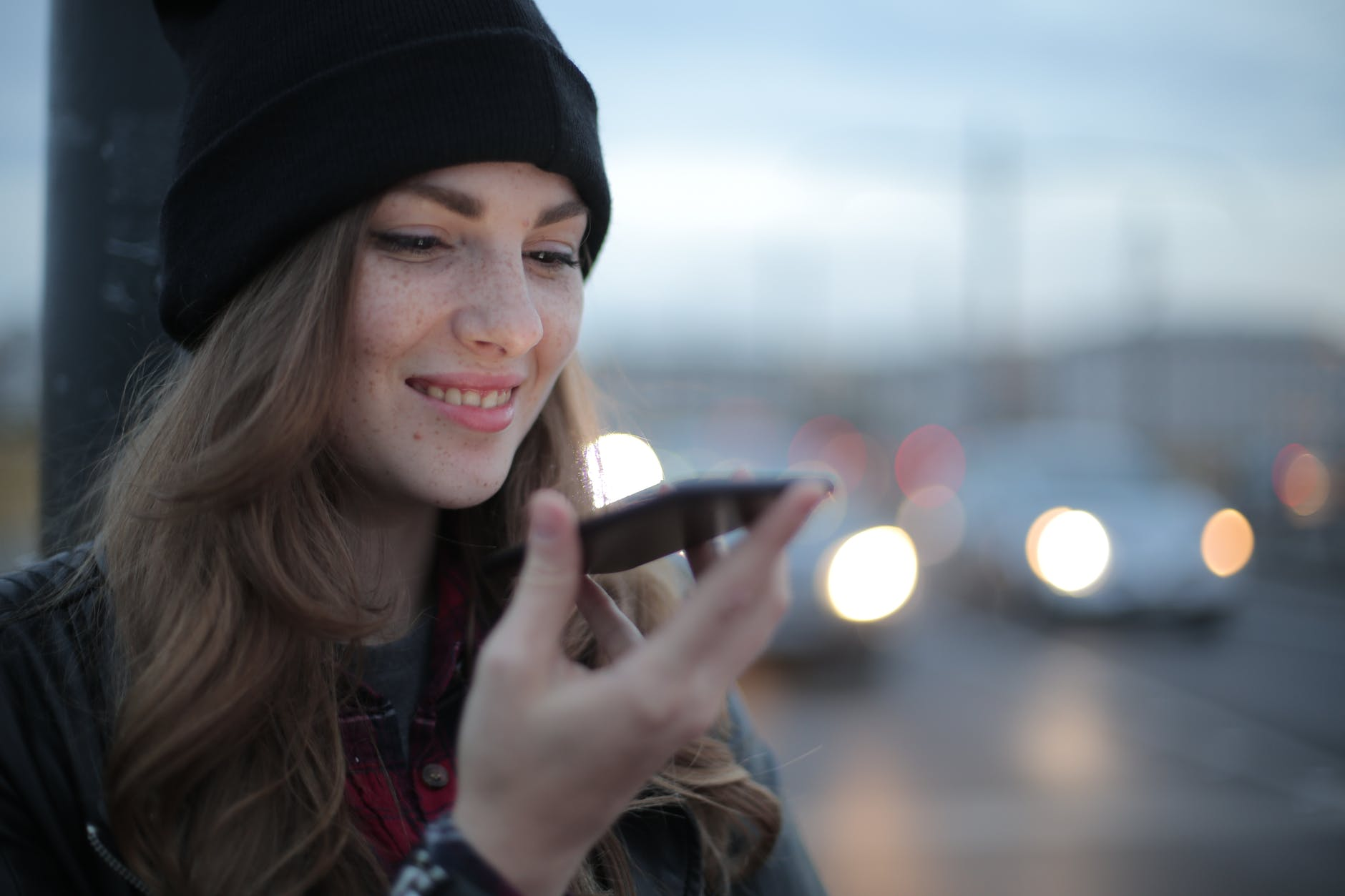 joyful young woman phoning on street in evening