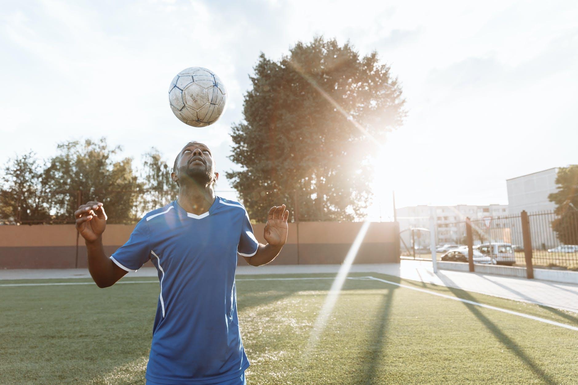 man in blue crew neck t shirt holding white soccer ball