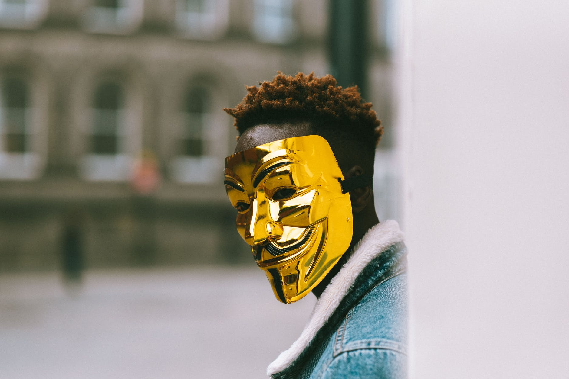 black activist in golden anonymous mask standing on city street